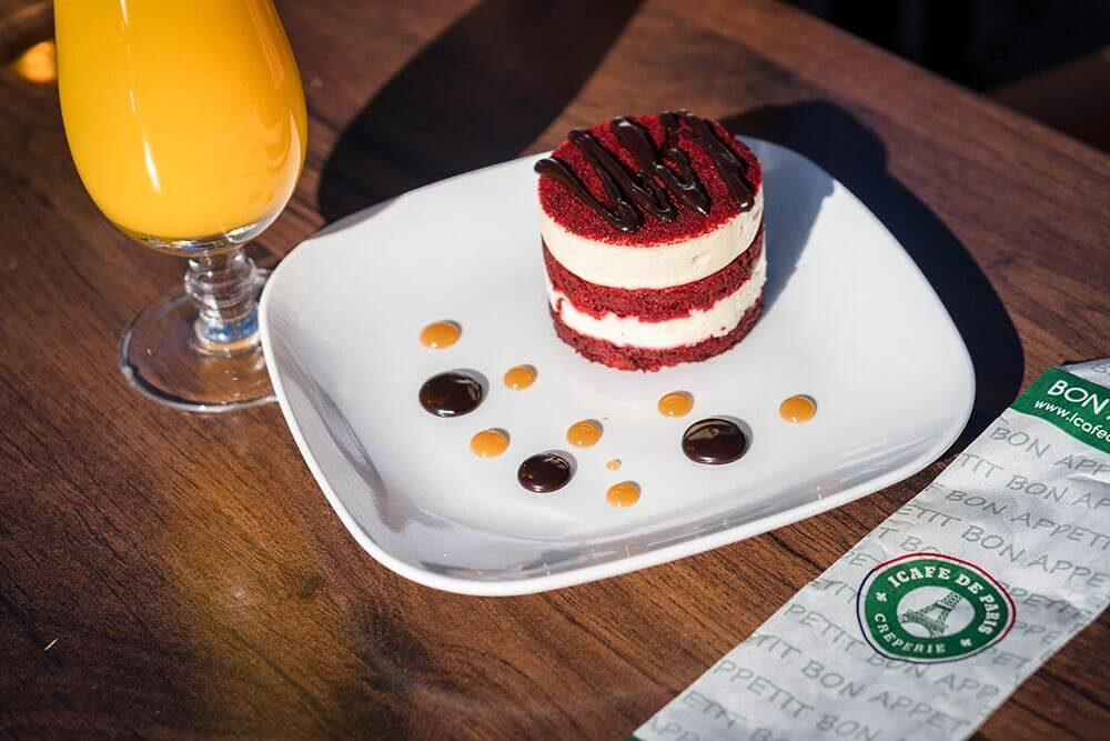 End your day with a glass of orange juice and a gourmet red velvet cake with vanilla frosting and chocolate caramel topping.