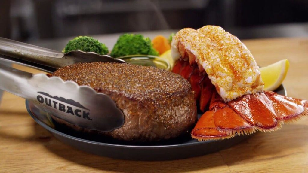 Outback Steakhouse at ICON Orlando serves an expertly grilled steak, a delicious lobster tail, and fresh steamed vegetables.