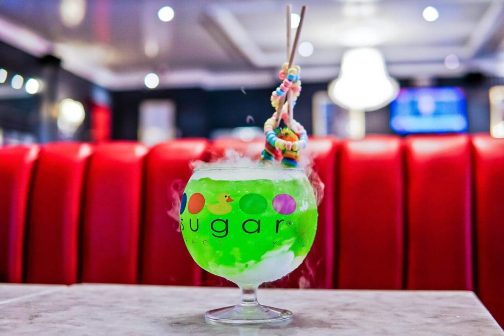 Sugar Factory serving a green candy infused smoking goblet cocktail with lollypops and candy necklaces for a fun night out.